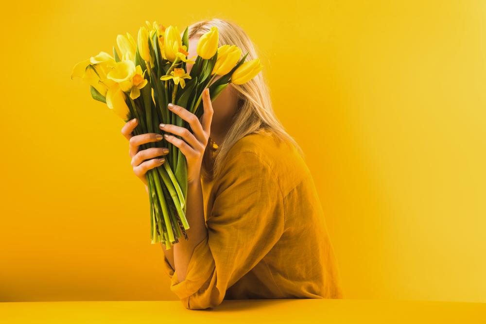 Фото дівчина тримає букет жовтих квітів на жовтому фоні