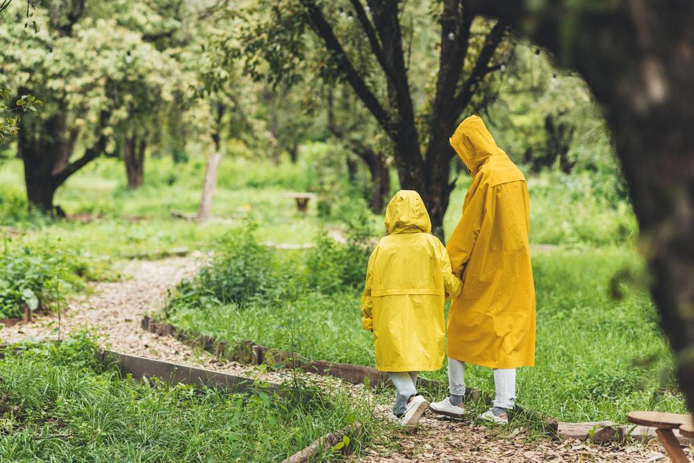 Фото двоє людей у жовтих дощовиках у парку