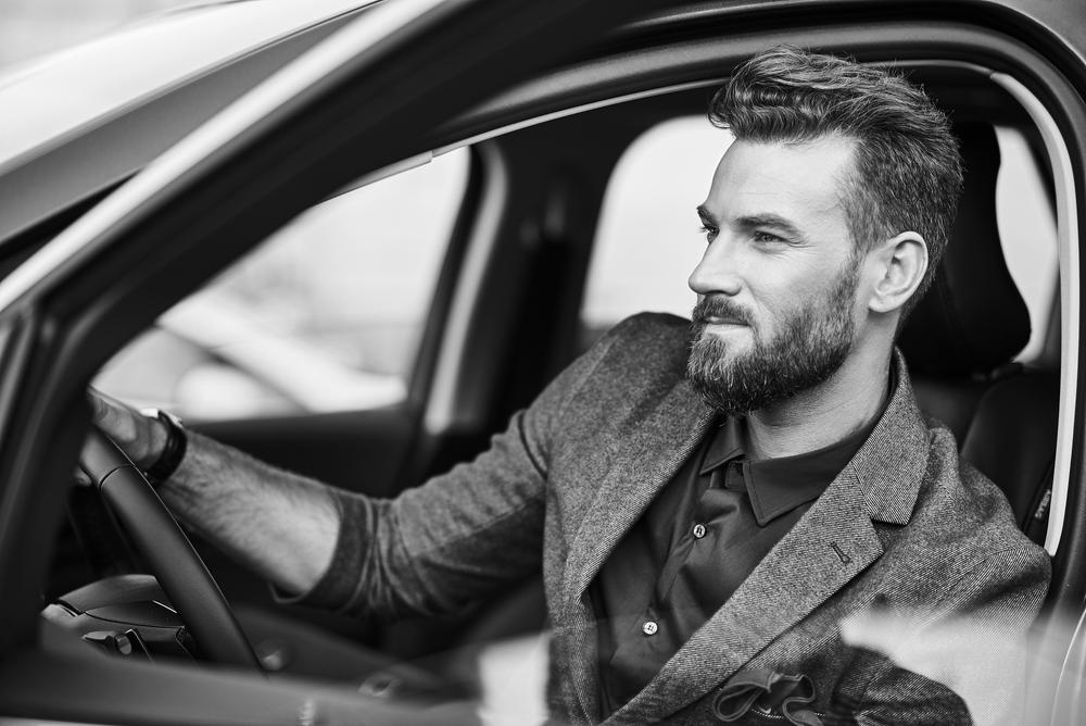 Фото чорно-біле стильний чоловік з бородою за кермом авто