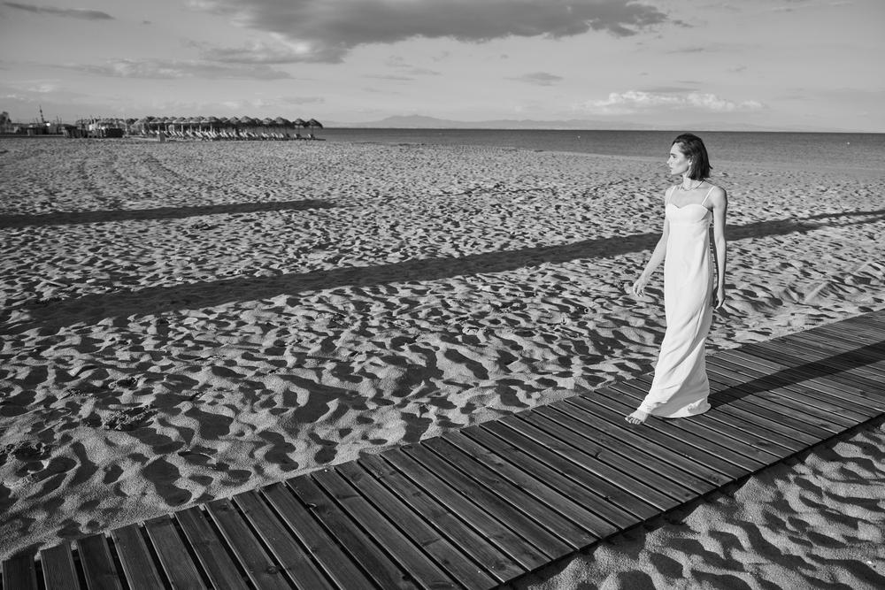 Фото чорно-біле жінка у білій сукні гуляє на пляжі