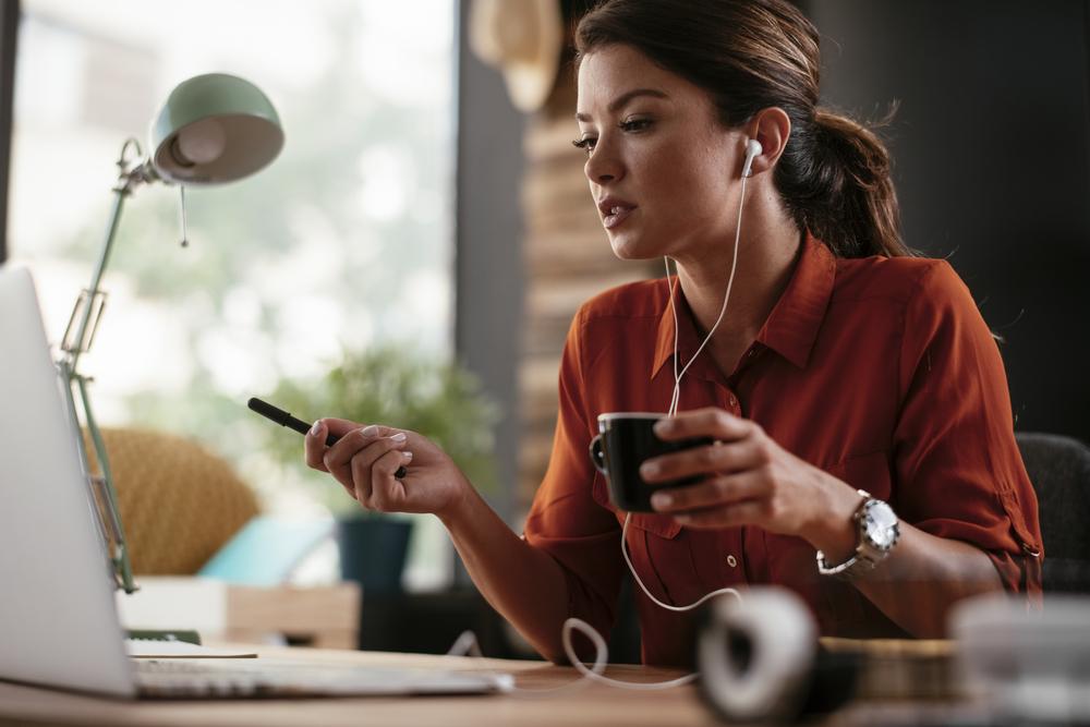 Фото жінка у навушниках дивиться на монітор ноутбука