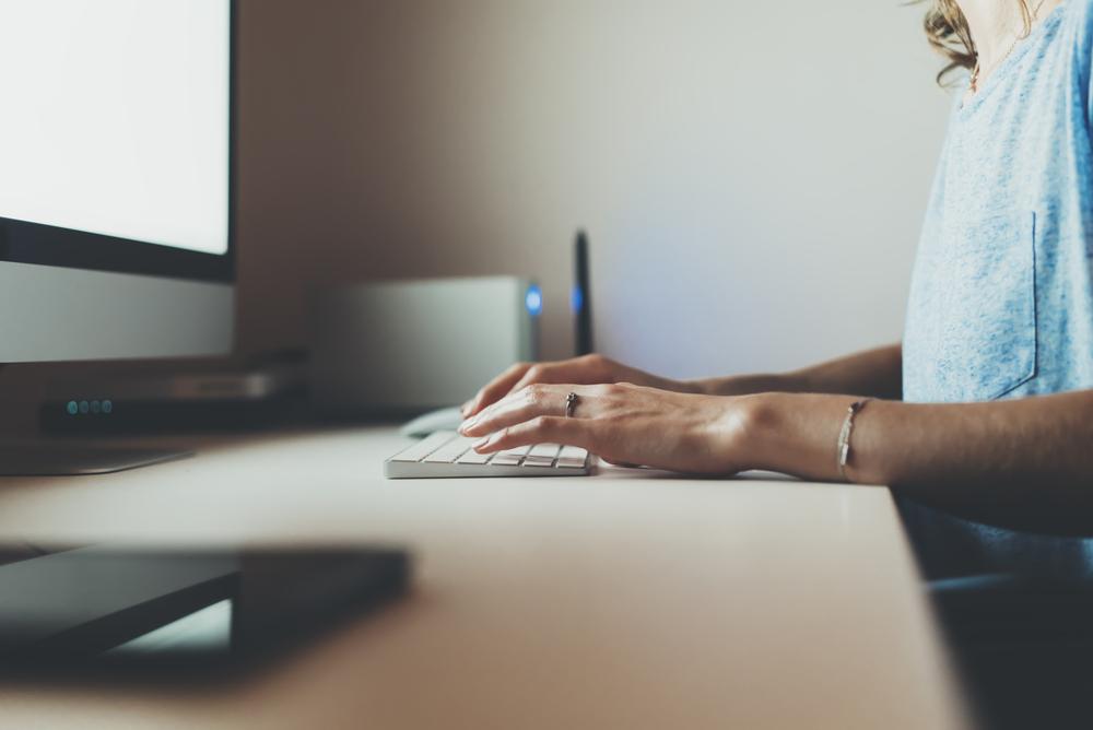Фото жінка друкує на клавіатурі