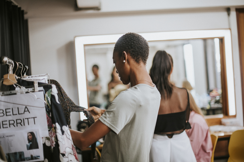 Фото стилістка вибирає одяг для моделі