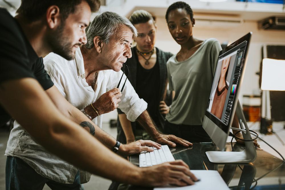 Фото група людей дивиться на фото моделі на екрані