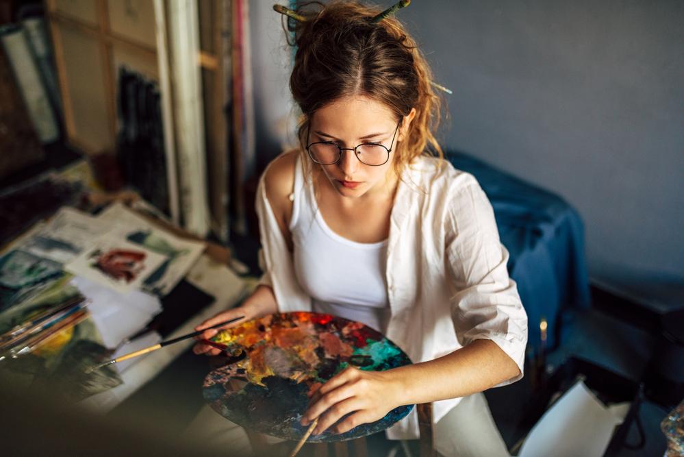 Фото художниця тримає палітру з фарбами