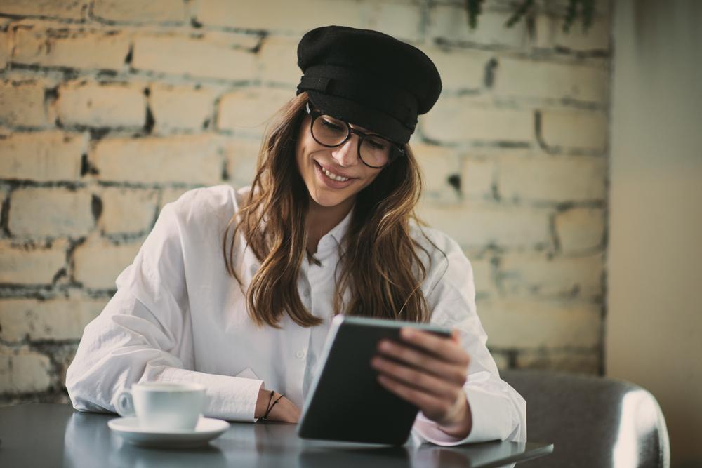 Фото молода жінка з планшетом у кафе