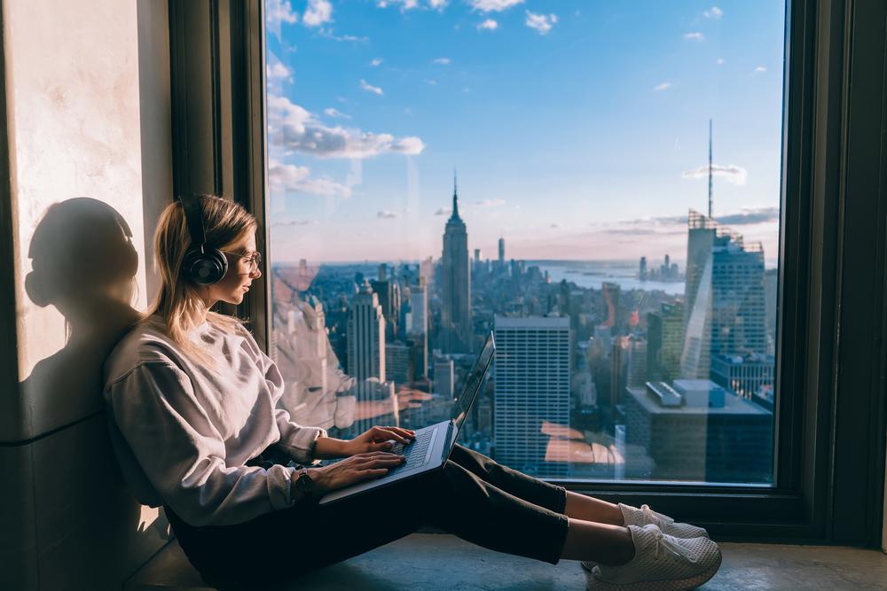 Фото дівчина з ноутбуком сидить біля вікна з гарним видом