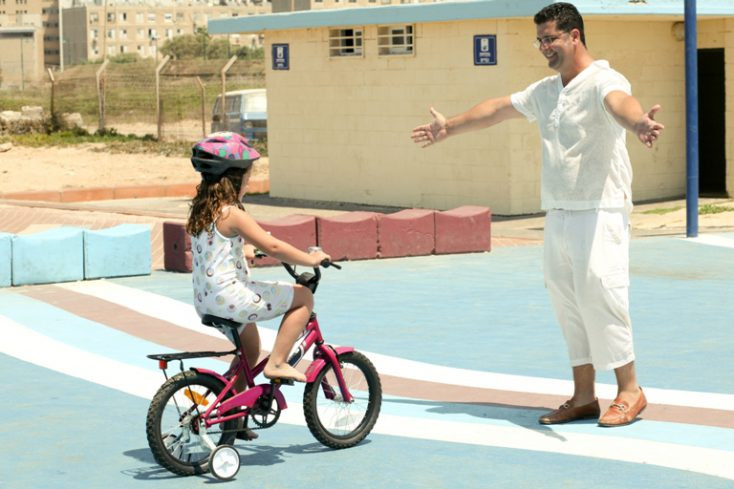 Trainer helping kid to learn bike riding © Depositphotos
