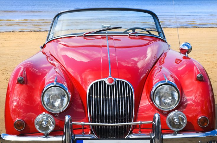 Old classic red car at the beach © Depositphotos