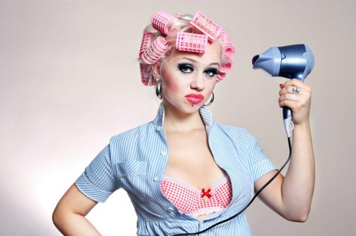 Cute girl styling hair © Depositphotos