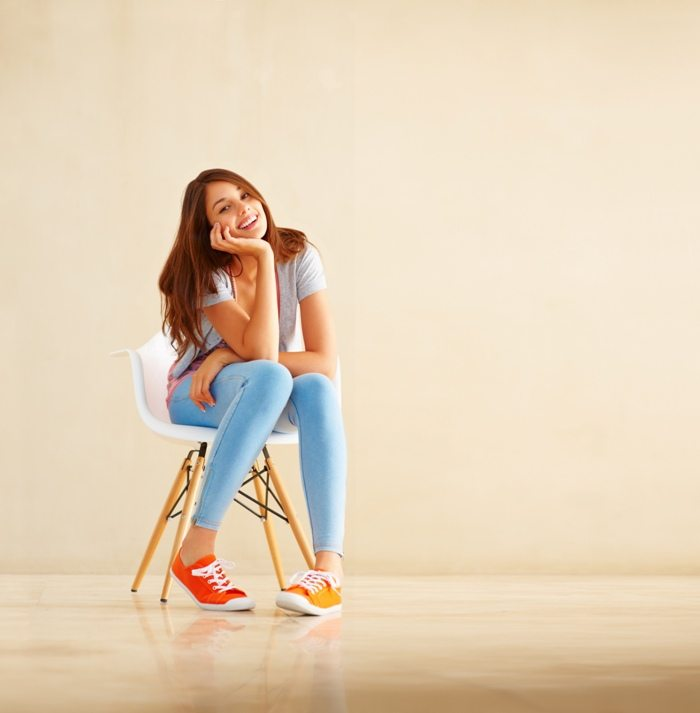 Girl sitting on chair and smiling © Depositphotos