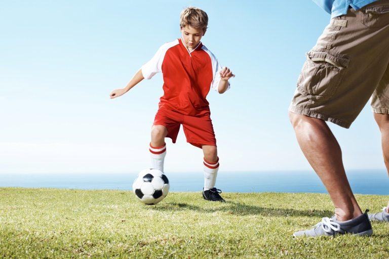 Small boy playing a soccer game with a man © Depositphotos