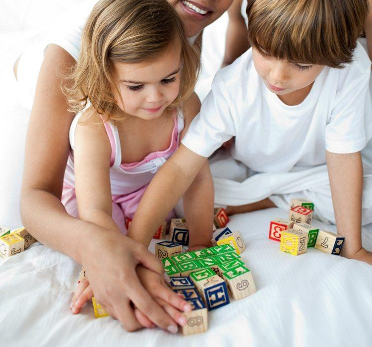 Close-up of brother and sister playing with cube toys © Depositphotos