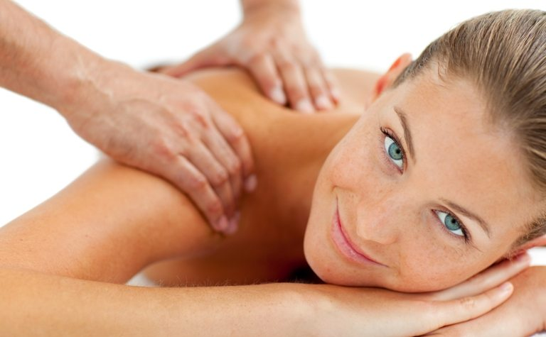 Smiling woman enjoying a massage © Depositphotos