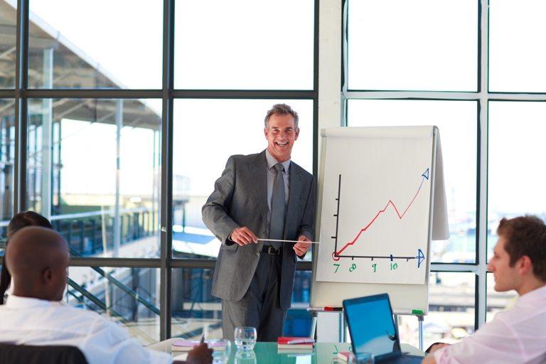 Mature businessman giving a presentation © Depositphotos