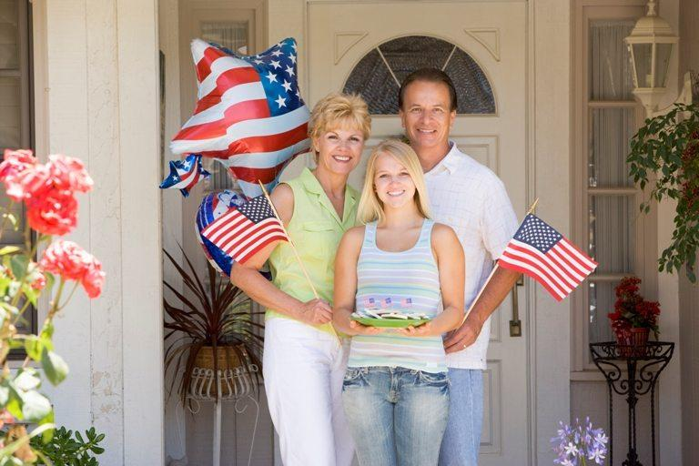 Family at front door on fourth of July with flags and cookies sm © Depositphotos