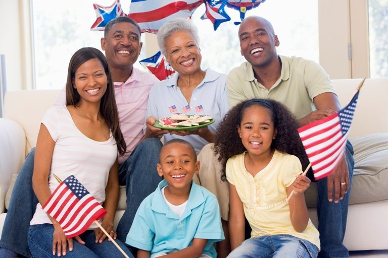Family in living room on fourth of July with flags and cookies s © Depositphotos