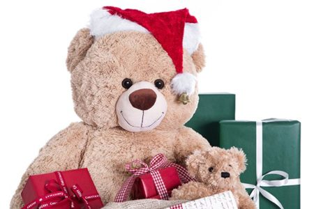Teddy bear wearing Christmas hat with gifts isolated on white ba