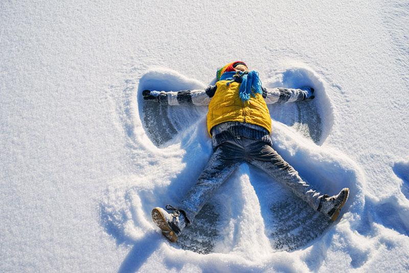 Boy making a snow angel