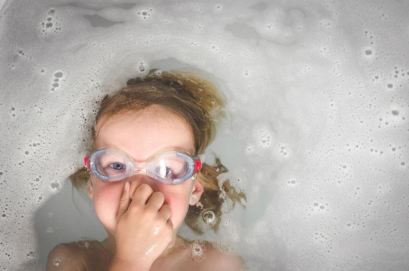 Boy with goggles playing in bathtub