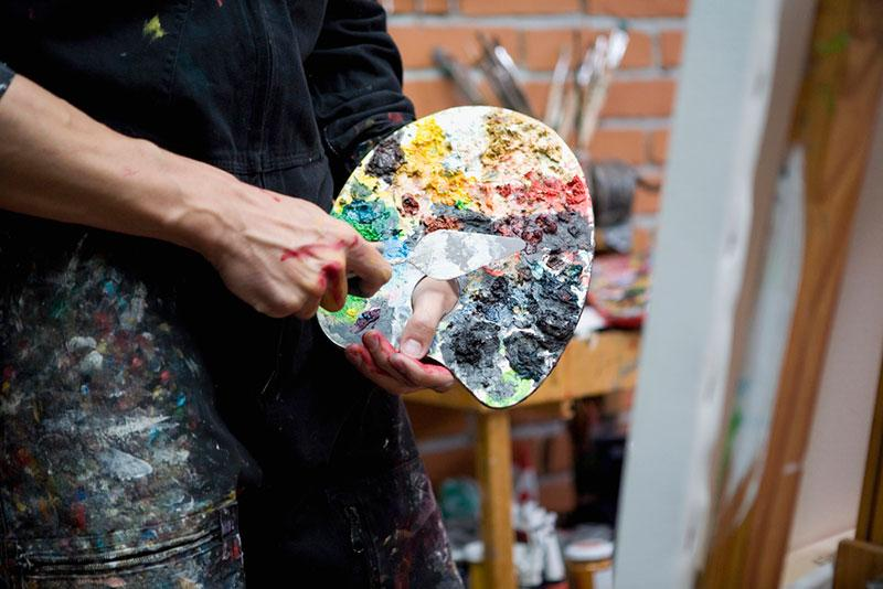 Midsection of artist holding palette and painting knife
