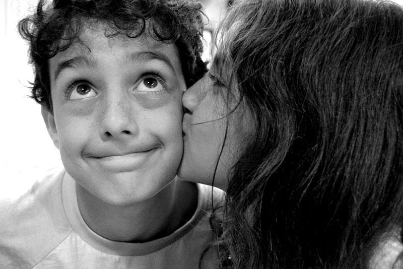 Close up portrait of Girl kissing boy on the cheek