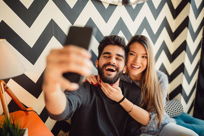 Nebojsa Tatomirov stock photography   Young man with beard taking selfie with girlfriend while sitting in cafe