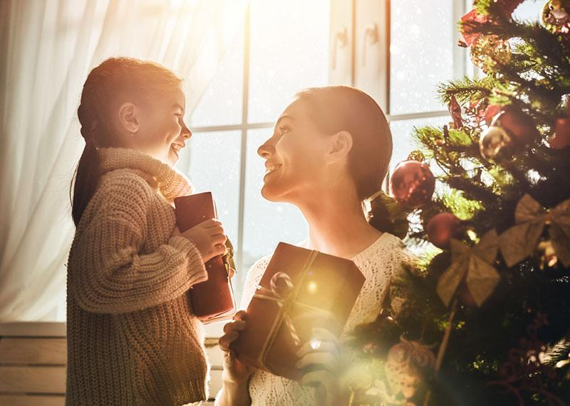 mother and daughter exchanging gifts on Christmas