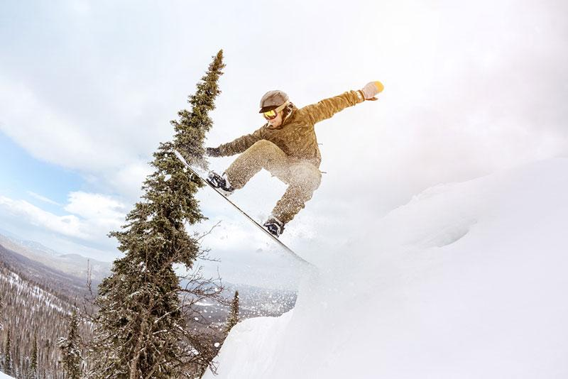 Snowboarder jump offpiste forest freeride