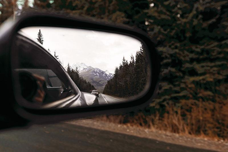 Reflection in a car mirror of mountains, caron the road and pine forest. Grey winter clouds. Cold north weather.