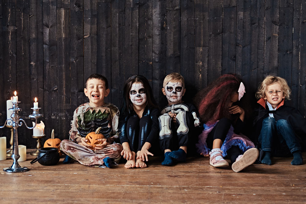 Halloween party with group children who sitting together on a wooden floor in an old house. Halloween concept.