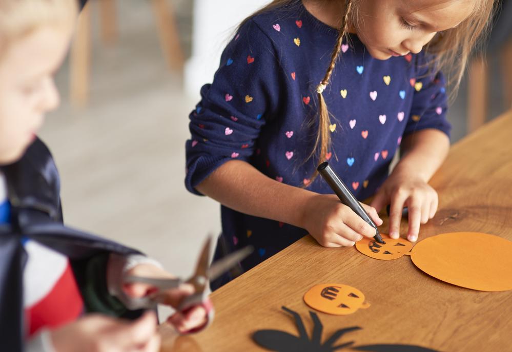 Cute girl preparing halloween decorations