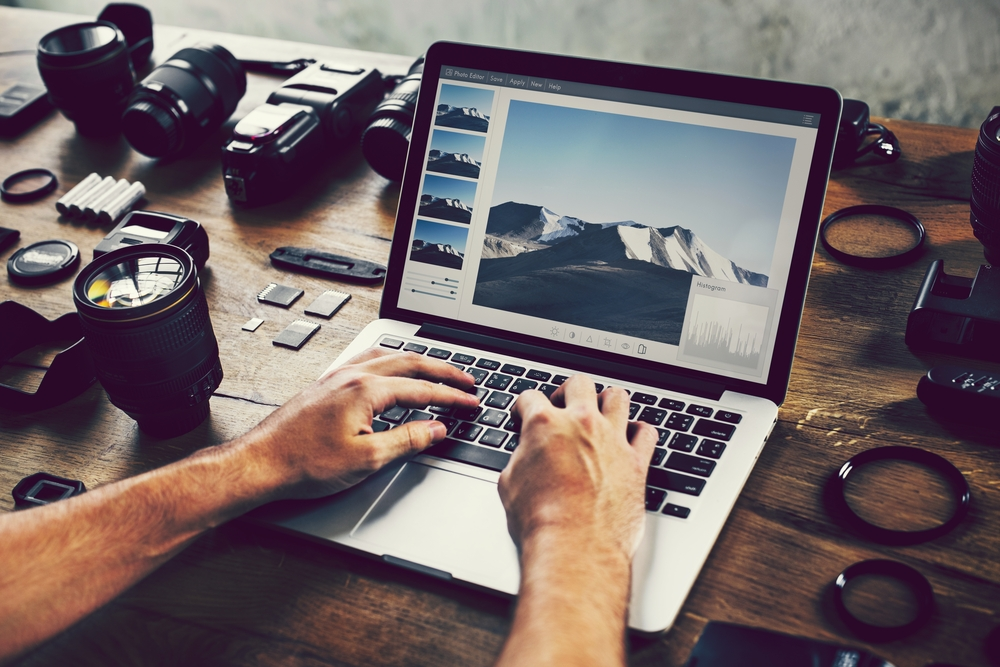 Photographer editing photos on a laptop