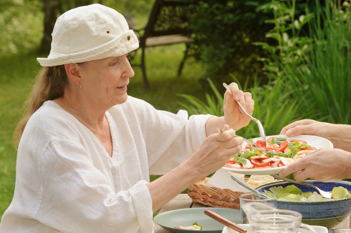 Senior woman eating outdoors stock photo