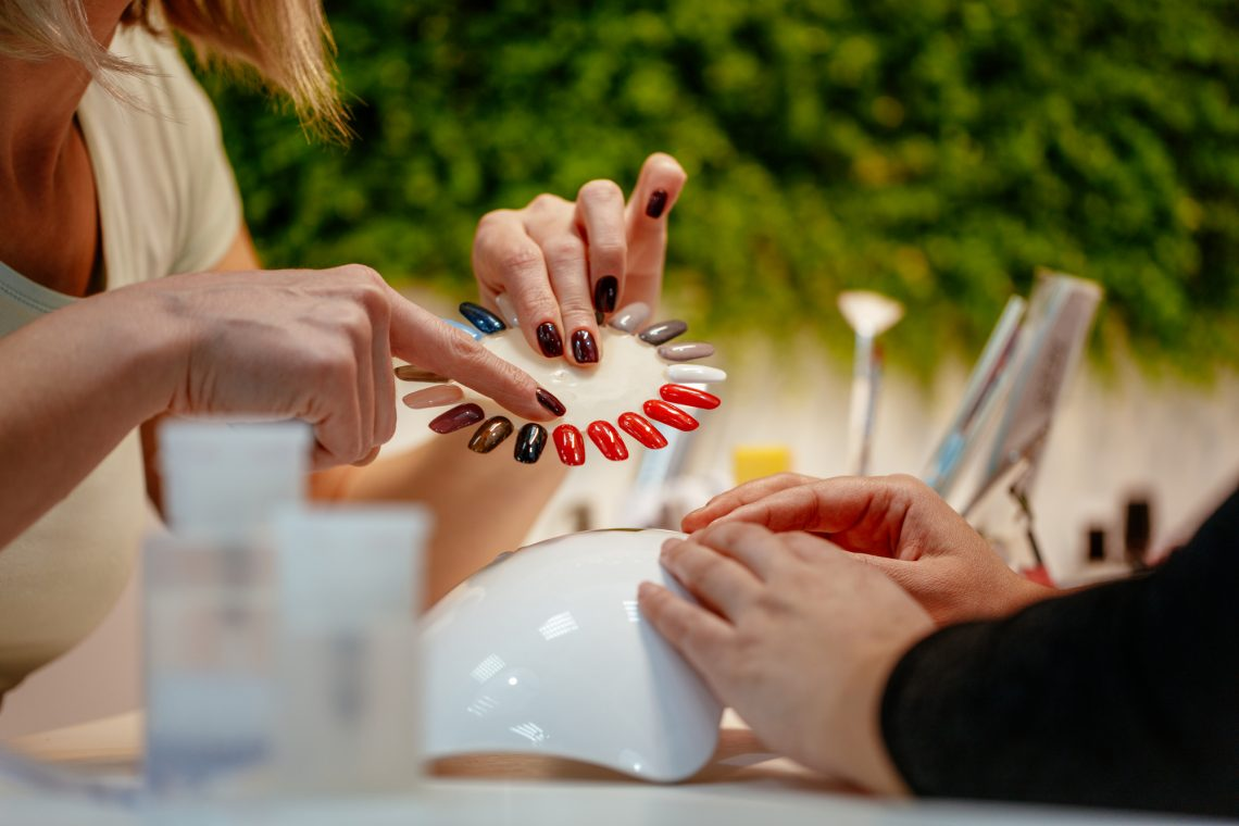 Close-up of woman choosing colours nails at the beauty salon
