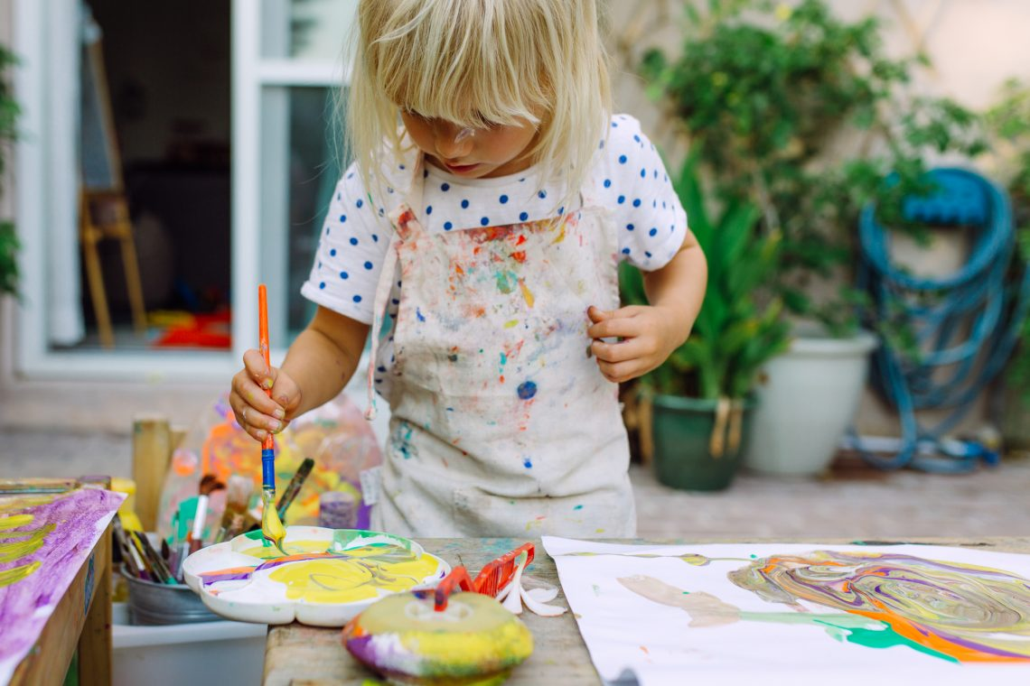 Little cute girl painting in the garden and mixing different colors