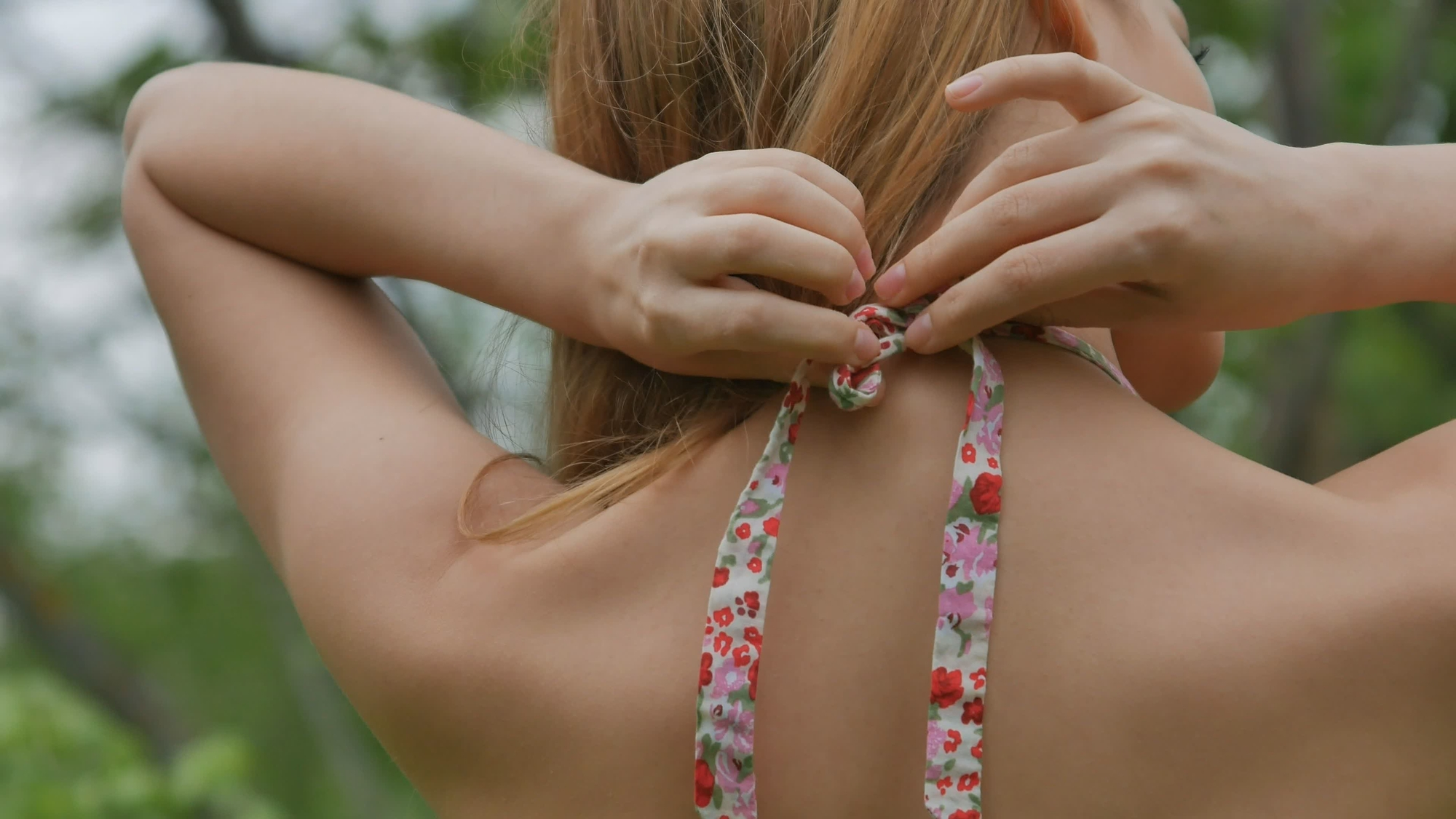 girl tying braid for clothes in the neck close up rear view