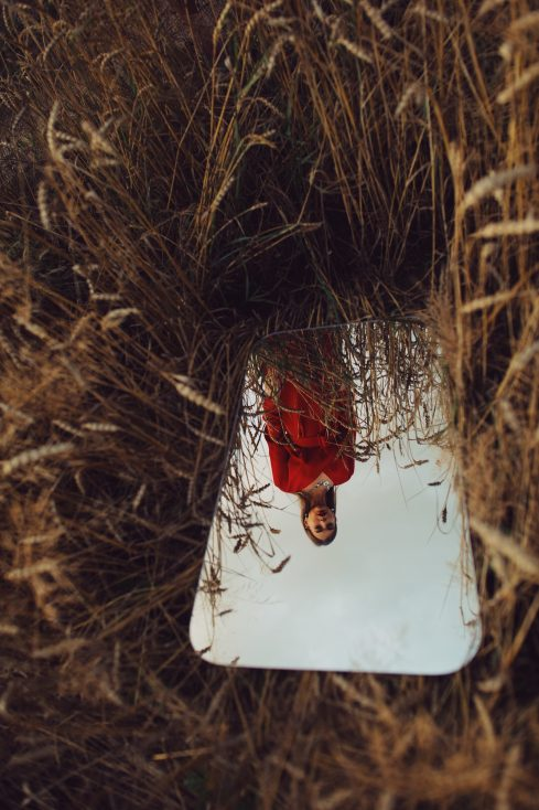 stock photo of woman in red dress in the mirror reflection