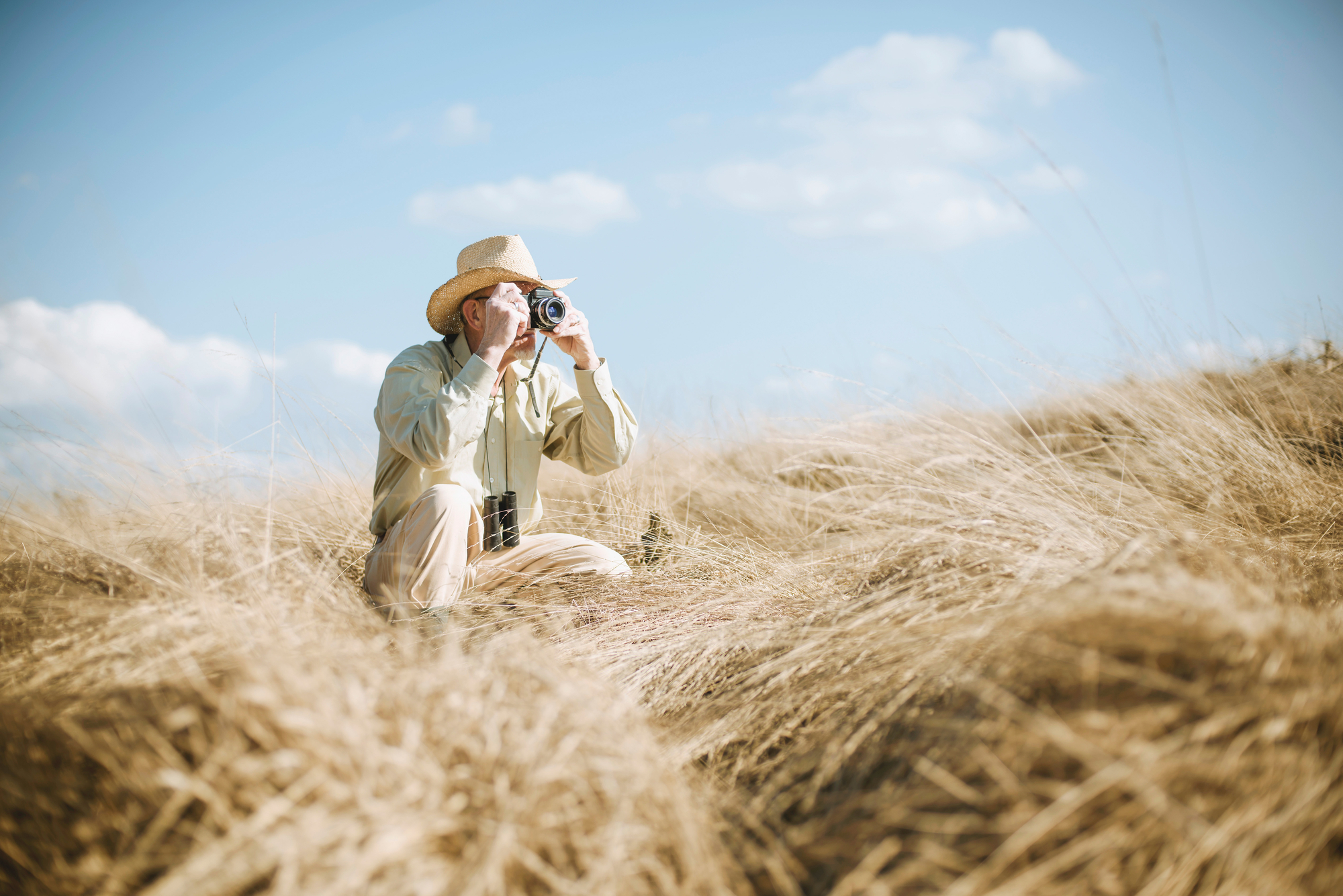 stock photo Senior safari man in the field taking picture