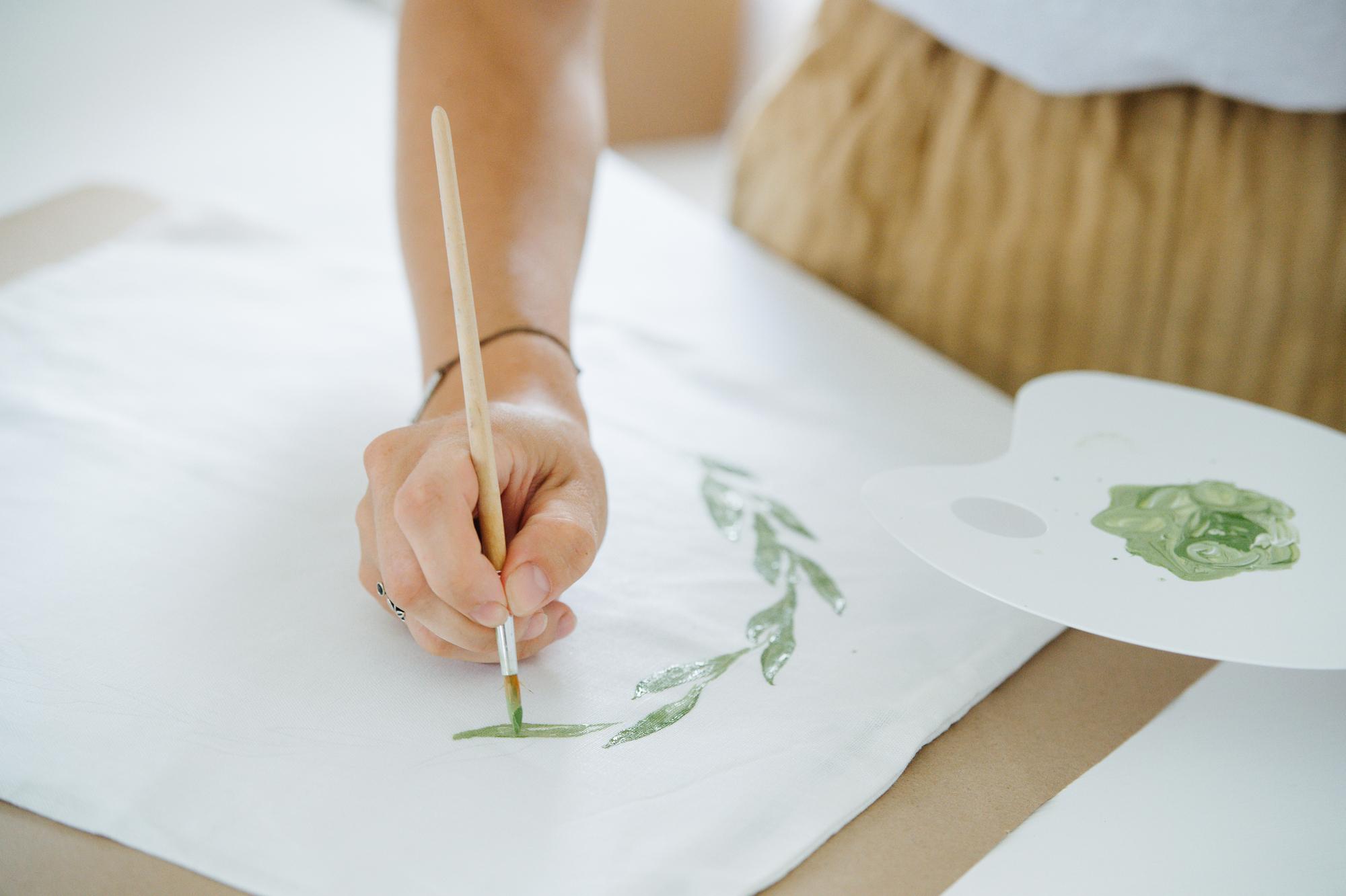 close-up hands paint a floral ornament