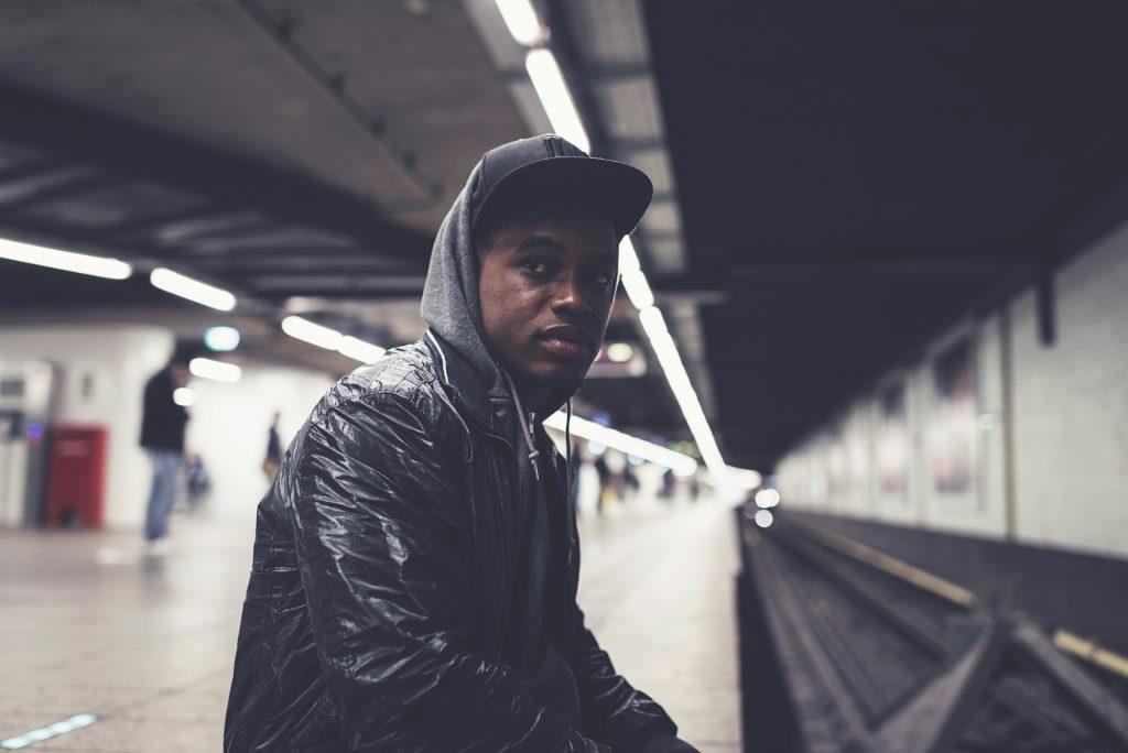 Urban fashion afro man sitting stock image