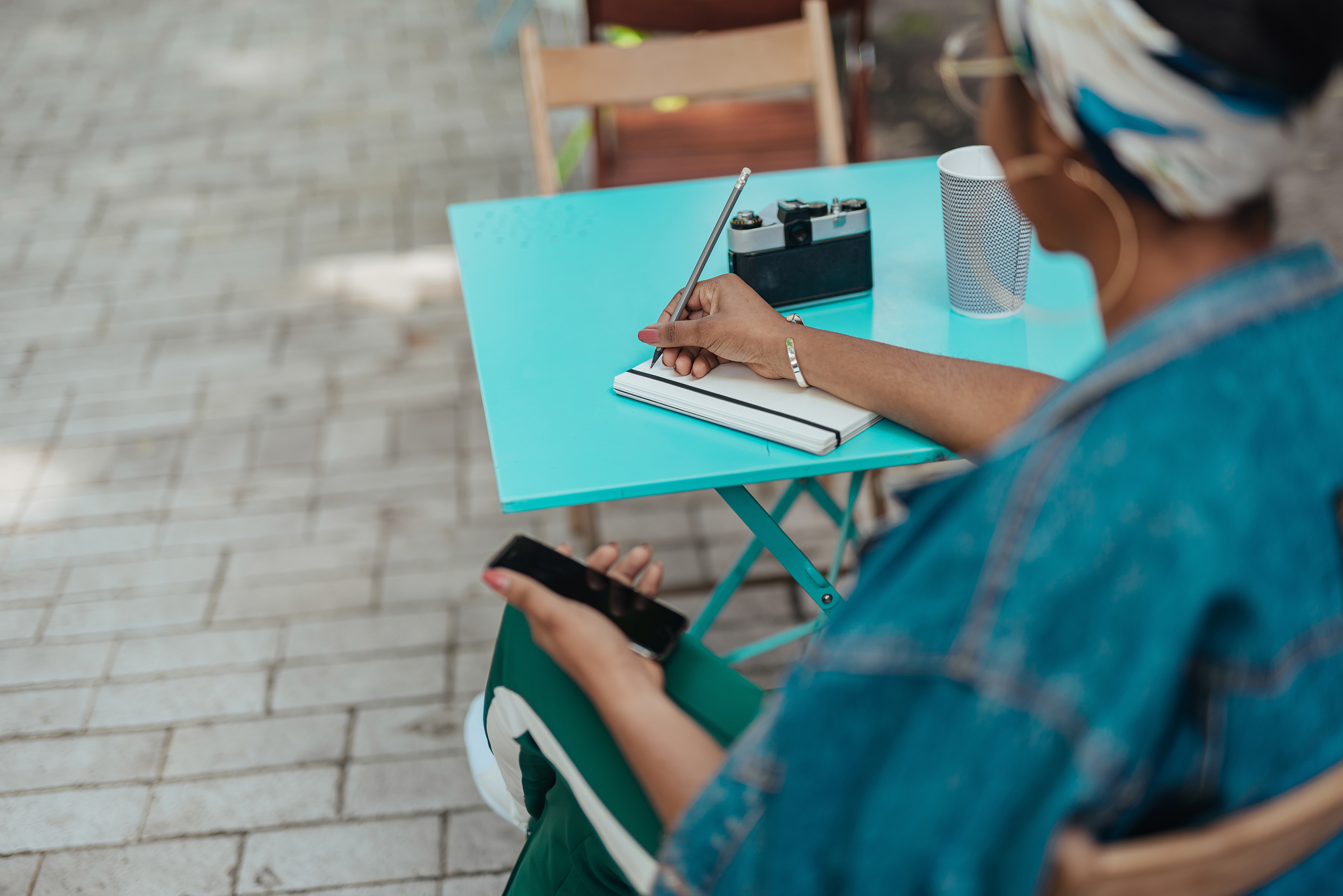 African american female sitting on terrace with notepad stock photo