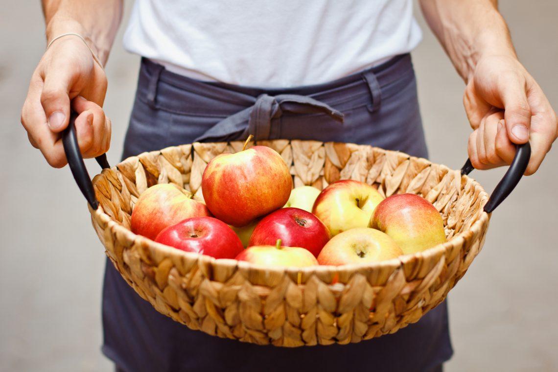 stock photo Ripe garden apples in a basket in female hands closeup