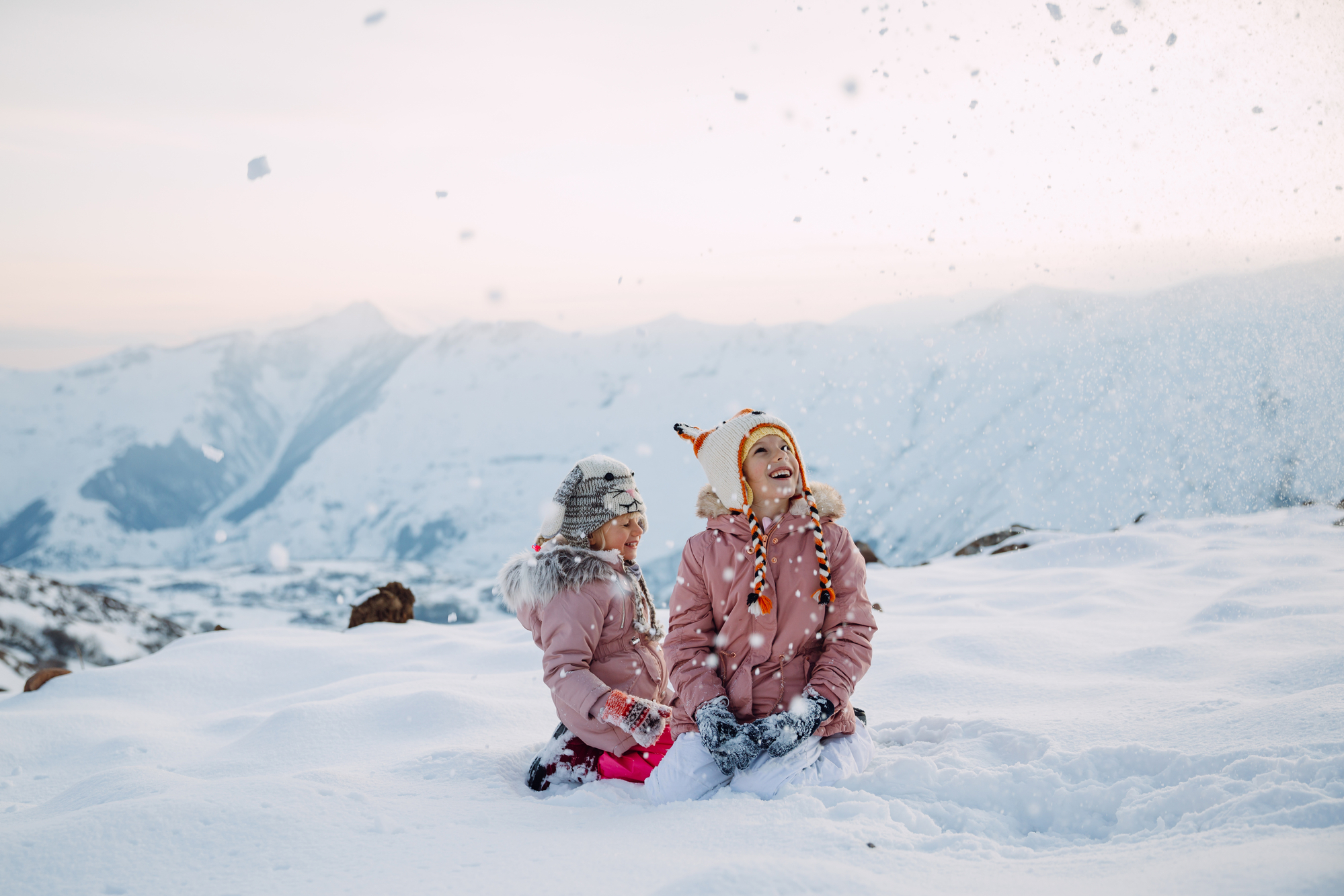 Two girls sitting in the snow and loooking at snowflakes falling