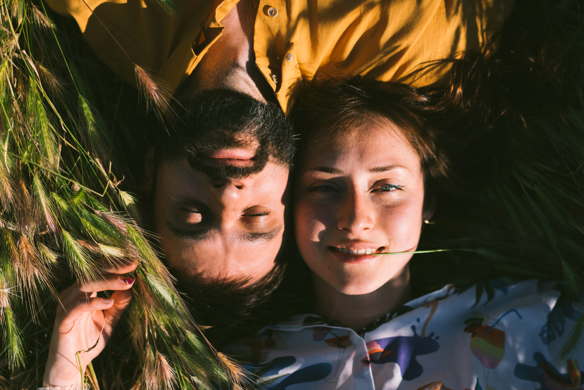 A romantic couple is enjoying warm sunny summer day while lying down amidst the meadow. A man and a woman in love are spending the weekend outdoors. Portrait of a young couple just married.