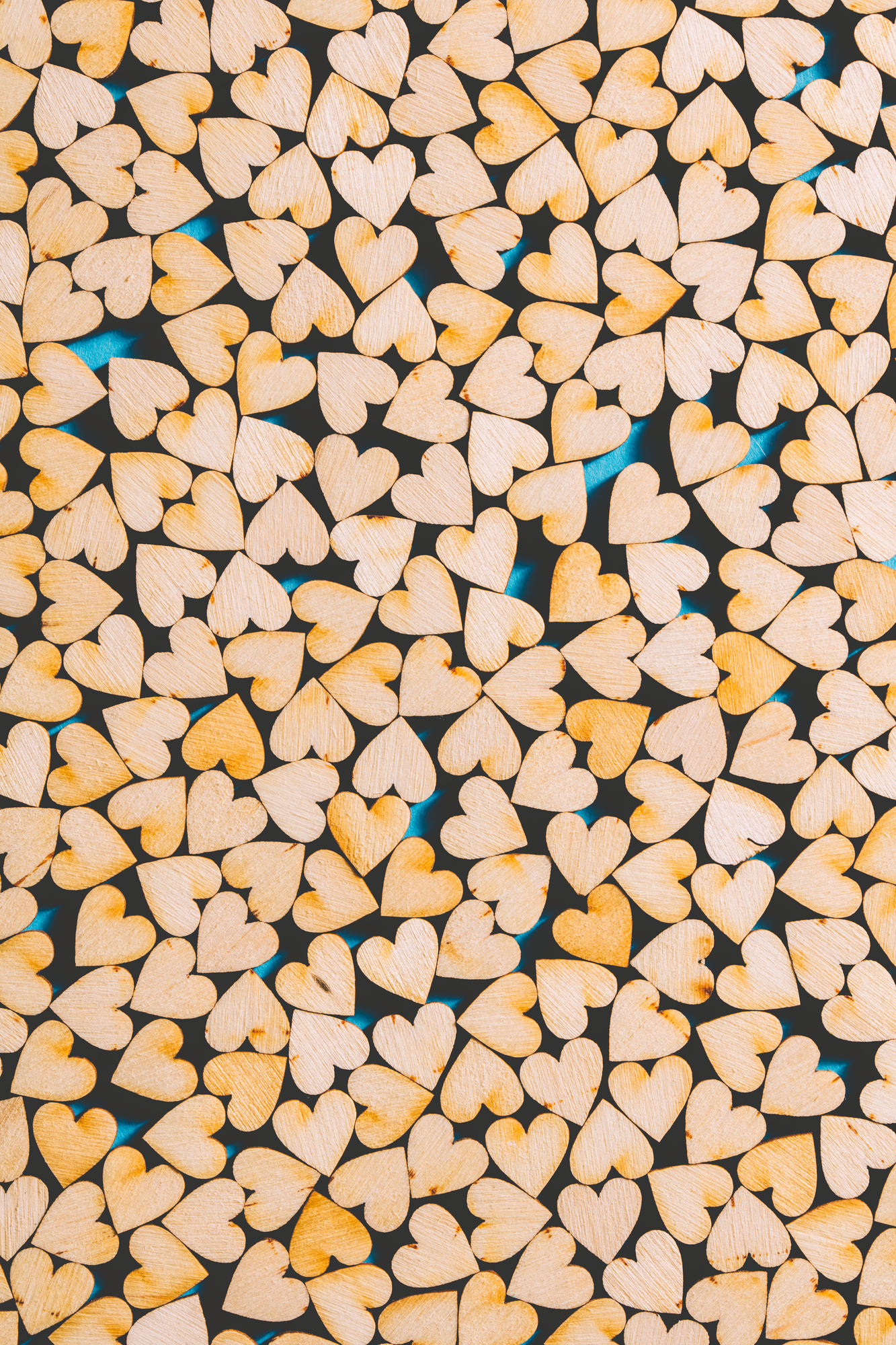 Little wooden hearts on blue background.