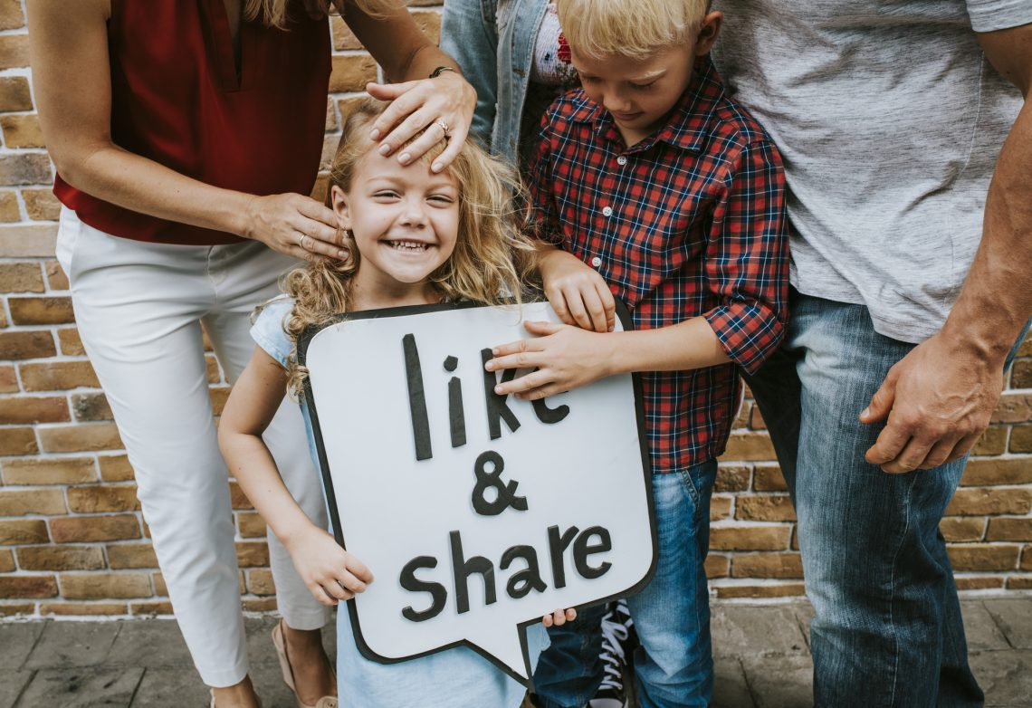 Children smiling holding a sign stock photo